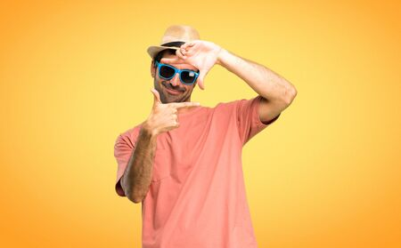 Man with hat and sunglasses on his summer vacation focusing face. Framing symbol on orange background