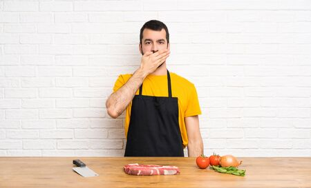 Chef holding in a cuisine covering mouth with hands