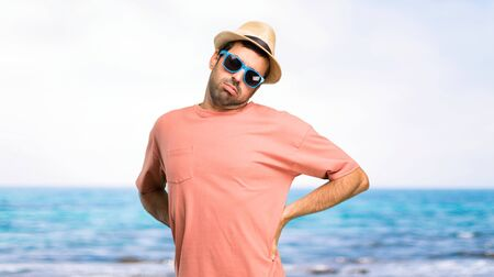 Man with hat and sunglasses on his summer vacation unhappy and suffering from backache for having made an effort at the beach Stock fotó