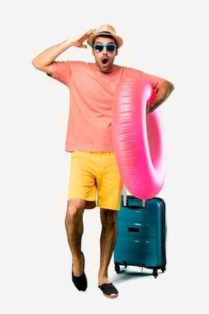 A full-length shot of Man with hat and sunglasses on his summer vacation with surprise and shocked facial expression. Gaping because can not believe what is happening on isolated background