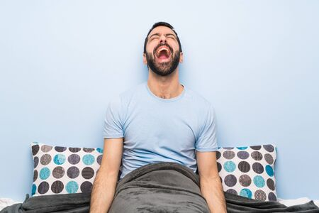 Man in bed shouting to the front with mouth wide open