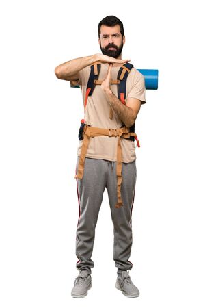 Hiker man making time out gesture over isolated white background