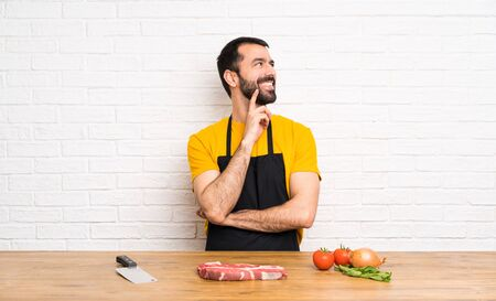 Chef holding in a cuisine thinking an idea while looking up