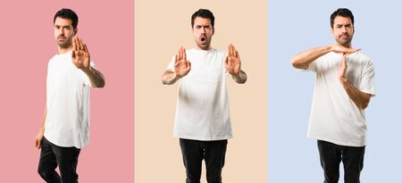 Set of Young man with white shirt making stop gesture with her hand for disappointed with an opinion on colorful background 스톡 콘텐츠