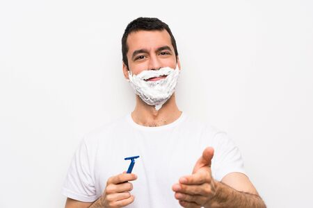 Man shaving his beard over isolated white background shaking hands for closing a good deal 写真素材