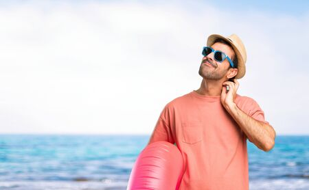 Man with hat and sunglasses on his summer vacation standing and thinking an idea while scratching head at the beach Banco de Imagens