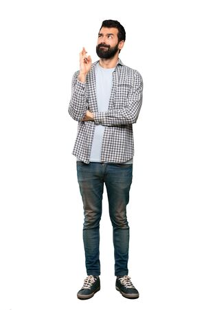 Handsome man with beard with fingers crossing and wishing the best over isolated white background Imagens