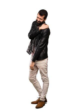 Gut aussehender Mann mit Bart, der unter Schmerzen in der Schulter leidet, weil er sich über isolierten weißen Hintergrund angestrengt hat
