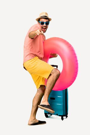 Full body of Man with hat and sunglasses on his summer vacation pointing with finger at someone and laughing a lot on isolated background