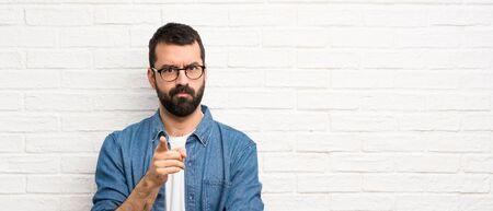 Hombre guapo con barba sobre pared de ladrillo blanco frustrado y apuntando hacia el frente