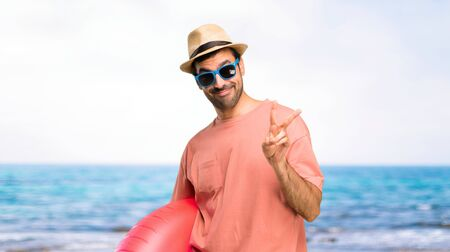 Man with hat and sunglasses on his summer vacation happy and counting two with fingers at the beach