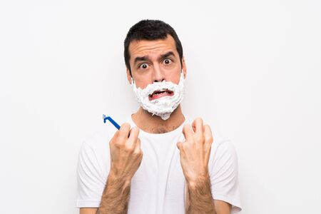 Man shaving his beard over isolated white background frustrated by a bad situation