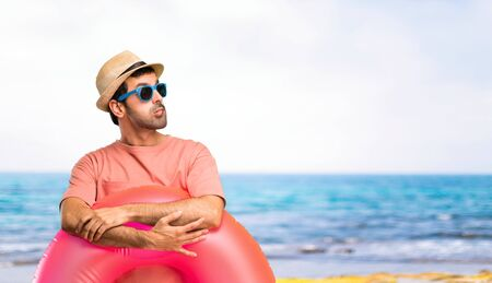 Man with hat and sunglasses on his summer vacation having doubts and with confuse face expression while bites lip. Questioning an idea at the beach Stock Photo - 124925137