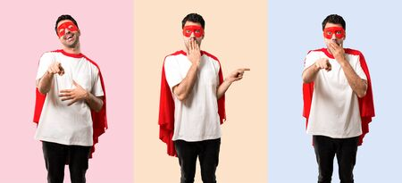 Set of Superhero man with mask and red cape pointing finger to the side and to the front and presenting a product with a surprised face while covering mouth on colorful background