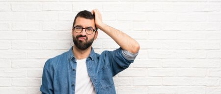 Handsome man with beard over white brick wall with an expression of frustration and not understanding