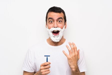 Man shaving his beard over isolated white background with surprise facial expression