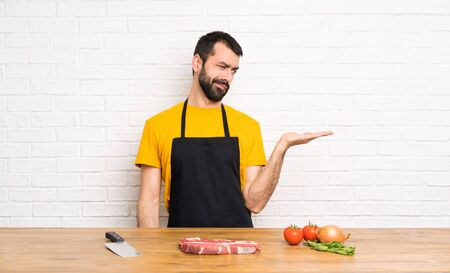 Chef holding in a cuisine holding copyspace with doubts
