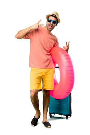 A full-length shot of Man with hat and sunglasses on his summer vacation showing tongue at the camera having funny look on isolated background