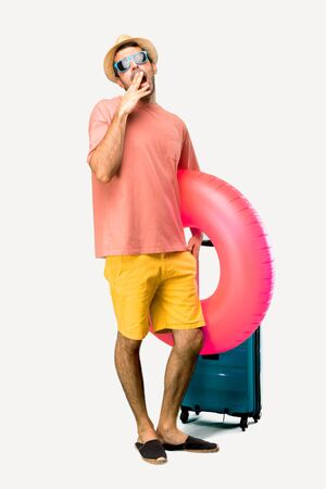 A full-length shot of Man with hat and sunglasses on his summer vacation yawning and covering wide open mouth with hand. Sleepy expression on isolated background