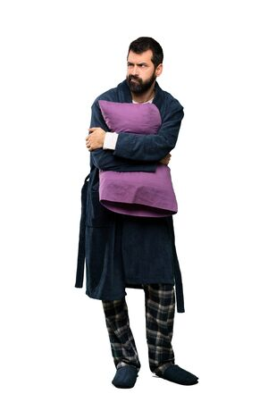 Man with beard in pajamas feeling upset over isolated white background