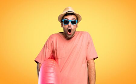 Man with hat and sunglasses on his summer vacation with surprise and shocked facial expression. Gaping because have just surprised with a gift on orange background