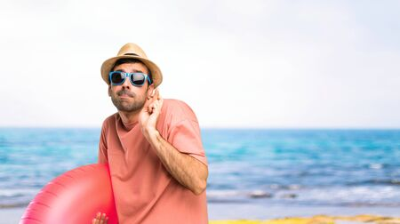 Man with hat and sunglasses on his summer vacation with fingers crossing and wishing the best. Making a wish. at the beach Imagens