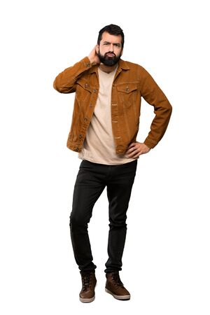 Handsome man with beard having doubts over isolated white background Imagens