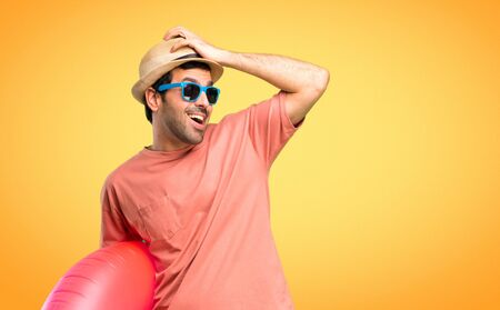 Man with hat and sunglasses on his summer vacation has just realized something and has intending the solution on orange background