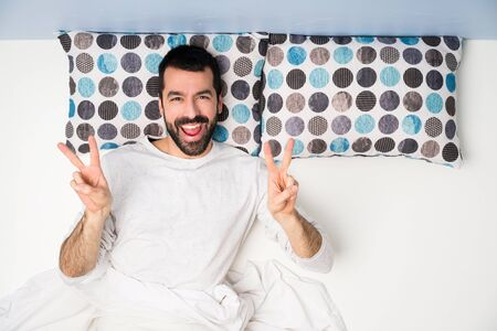 Man in bed in top view showing victory sign with both hands