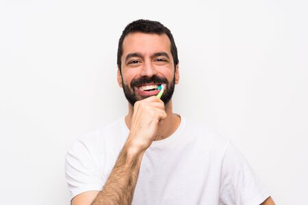 Man with beard brushing teeth over isolated white background Banco de Imagens
