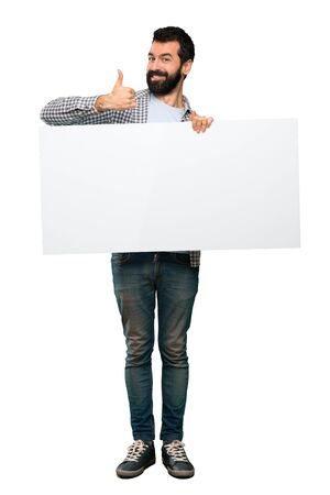 Happy Handsome man with beard holding an empty placard over isolated white background Zdjęcie Seryjne