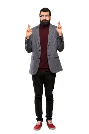 Handsome man with glasses with fingers crossing and wishing the best over isolated white background