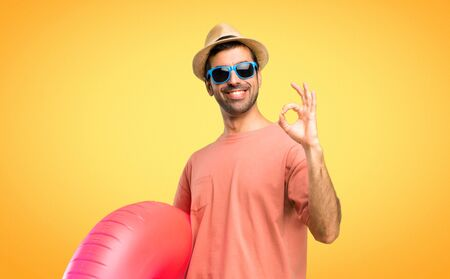 Man with hat and sunglasses on his summer vacation showing an ok sign with fingers. Face of happiness and satisfaction on orange background
