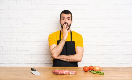 Chef holding in a cuisine surprised and shocked while looking right Imagens