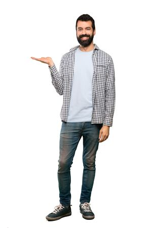 Handsome man with beard holding copyspace imaginary on the palm to insert an ad over isolated white background Archivio Fotografico