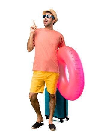 Full body of Man with hat and sunglasses on his summer vacation standing and thinking an idea pointing the finger up on isolated background