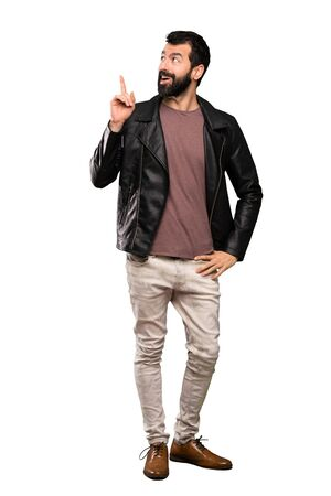 Handsome man with beard thinking an idea pointing the finger up over isolated white background