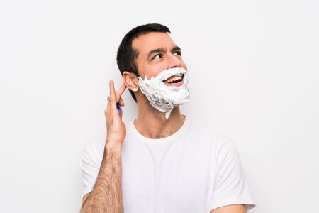 Man shaving his beard over isolated white background thinking an idea