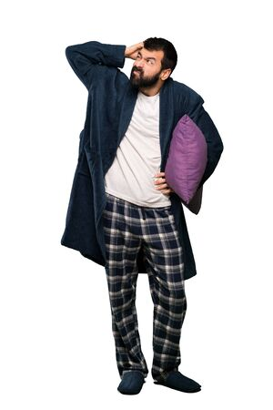 Man with beard in pajamas having doubts while scratching head over isolated white background Stock Photo