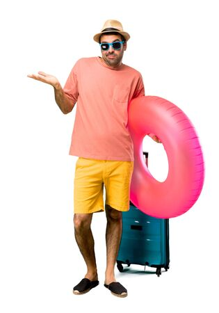 A full-length shot of Man with hat and sunglasses on his summer vacation unhappy and frustrated with something because not understand something. Negative facial expression on isolated background