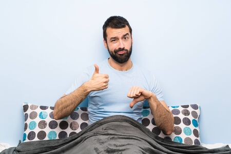 Man in bed making good-bad sign. Undecided between yes or not