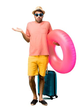 Full body of Man with hat and sunglasses on his summer vacation having doubts and with confuse face expression while raising hands and shoulders Uncertain concept on isolated background