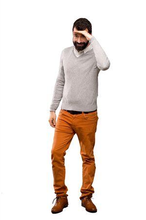 Hombre guapo mirando lejos con la mano para mirar algo sobre fondo blanco aislado Foto de archivo