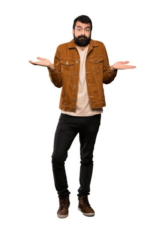 Handsome man with beard having doubts while raising hands over isolated white background Stock Photo
