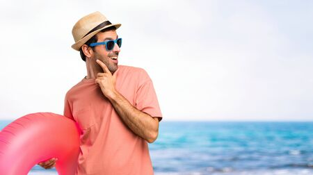 Man with hat and sunglasses on his summer vacation standing and looking to the side with the hand on the chin at the beach