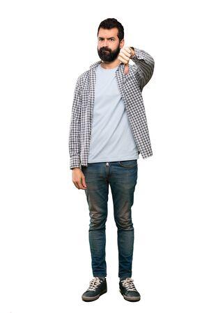 Bell'uomo con la barba che mostra il pollice verso il basso con espressione negativa su sfondo bianco isolato
