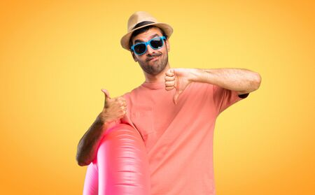 Man with hat and sunglasses on his summer vacation making good-bad sign. Undecided person between yes or not on orange background