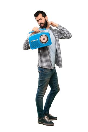 Handsome man with beard holding a radio over isolated white background