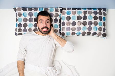Man in bed in top view having doubts Stock Photo - 124836310