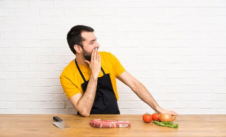 Chef holding in a cuisine shouting with mouth wide open to the lateral